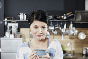Portrait of woman in kitchen with cup of coffeeの写真素材 [FYI04339897]