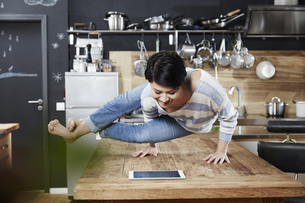 Woman doing a handstand on table in kitchen looking on tableの写真素材 [FYI04339899]