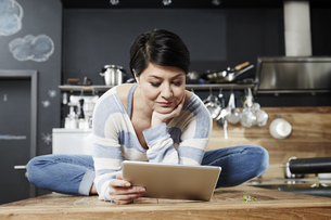 Woman sitting on table in kitchen looking on tabletの写真素材 [FYI04339900]
