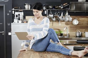 Woman sitting on table in kitchen looking on tabletの写真素材 [FYI04339901]