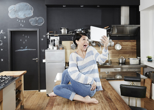 Woman sitting on table in kitchen taking a selfie with tableの写真素材 [FYI04339902]