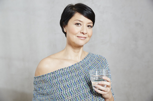 Portrait of confident woman holding glass of waterの写真素材 [FYI04339915]