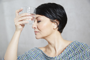 Woman holding glass of water to her foreheadの写真素材 [FYI04339916]