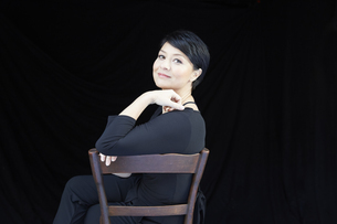 Portrait of smiling woman sitting on chairの写真素材 [FYI04339919]