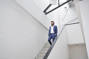 Smiling businessman walking down stairsの写真素材 [FYI04339923]