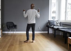 Mature man dancing alone at home, holding smart phoneの写真素材 [FYI04339926]