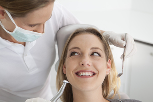Germany, Young woman getting her teeth examined by dentistの写真素材 [FYI04339987]