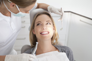 Germany, Young woman getting her teeth examined by dentistの写真素材 [FYI04339988]