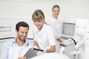 Germany, Dentist showing clipboard to patientの写真素材 [FYI04339998]