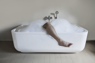Mid adult man in bathtub with leg outの写真素材 [FYI04340000]