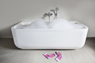Bathtub with soapsuds and socks in bathroomの写真素材 [FYI04340001]