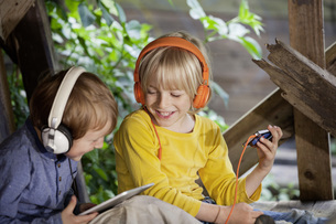Germany, North Rhine Westphalia, Cologne, Boys listening musの写真素材 [FYI04340021]
