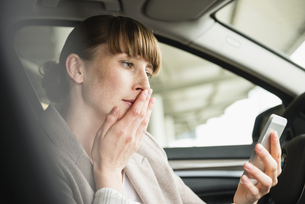 Portrait of businesswoman sitting in a car looking at her smの写真素材 [FYI04340041]