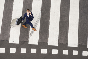 Germany, businesswoman with rolling suitcase walking on zebrの写真素材 [FYI04340044]