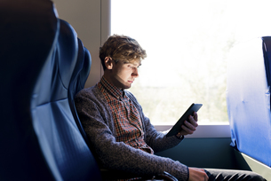 Young man sitting in a train looking at tabletの写真素材 [FYI04340063]