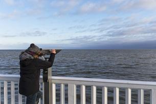 Germany, Cuxhaven, Tourist looking through binocularsの写真素材 [FYI04340301]