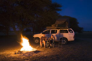 Africa, Botswana, Two persons by camp fireの写真素材 [FYI04340368]