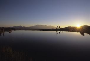 Austrian Alps, two people walking near river bankの写真素材 [FYI04340427]
