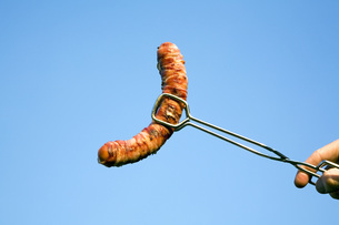 Man holding sausage with gripperの写真素材 [FYI04340565]