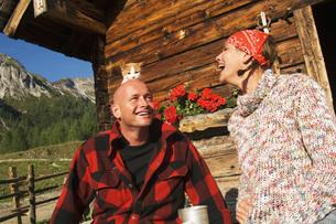 Couple sitting in front of alpine hutの写真素材 [FYI04340647]