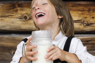Austria, Salzburger Land,Boy (8-9) drinking milk, laughing,の写真素材 [FYI04340681]