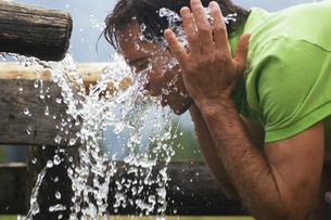 Brunette man drinking water, portraitの写真素材 [FYI04340693]