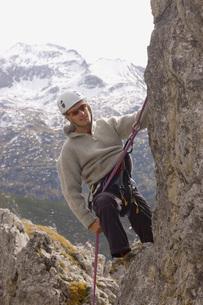 Austria, Salzburger Land, Man climbing on rock faceの写真素材 [FYI04340710]