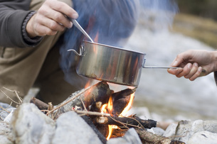 Austria, Salzburg county, Young couple cooking at campfireの写真素材 [FYI04340741]