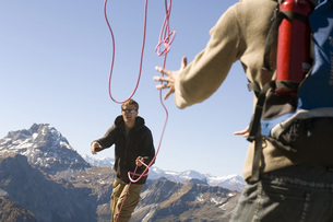 Austria, Salzburg County, Young couple using a rope as a safの写真素材 [FYI04340748]