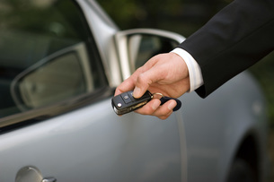 Person at car using remote control key, close-upの写真素材 [FYI04340771]
