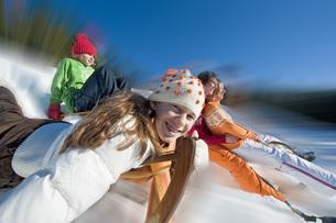 Austria, Salzburger Land, Altenmarkt, Family sleddingの写真素材 [FYI04340846]