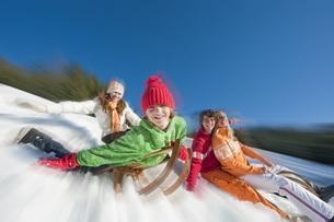 Austria, Salzburger Land, Altenmarkt, Family sleddingの写真素材 [FYI04340847]