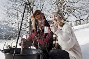 Austria, Salzburger Land, Couple cooking on campfireの写真素材 [FYI04340856]