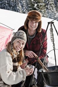 Austria, Salzburger Land, Couple cooking on campfireの写真素材 [FYI04340857]