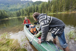 Austria, Obertauern, Young couple pushing kayak into lakeの写真素材 [FYI04340974]