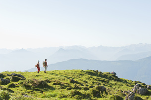 Young couple standing on mountaintop, looking at view.の写真素材 [FYI04340975]