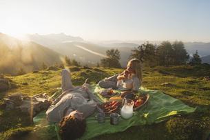 Young couple lying on blanket, having breakfast.の写真素材 [FYI04340978]