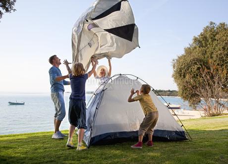 Croatia, Zadar, Family putting up tent at beachの写真素材 [FYI04341038]