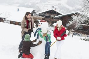 Austria, Salzburg, Huettau, Family with snowmanの写真素材 [FYI04341065]