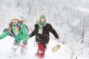 Austria, Salzburg, Huettau, Children walking through snowの写真素材 [FYI04341067]