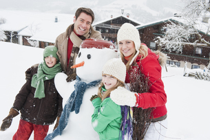 Austria, Salzburg, Huettau, Family with snowman, smilingの写真素材 [FYI04341069]