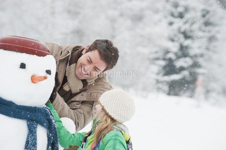 Austria, Salzburg, Huettau, Father and daughter with snowman,の写真素材 [FYI04341070]