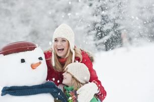 Austria, Salzburg, Huettau, Mother and daughter with snowman,の写真素材 [FYI04341071]