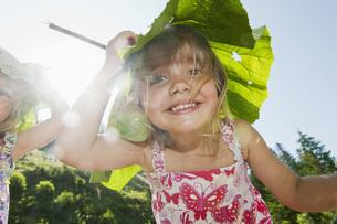 Austria, Salzburg, Girls carrying leaf on head, smilingの写真素材 [FYI04341168]