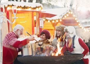 Austria, Salzburg, Senior man serving drink to young peopleの写真素材 [FYI04341177]