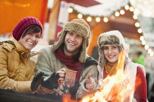 Austria, Salzburg, Man and women by fire at christmas marketの写真素材 [FYI04341180]
