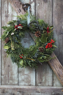 Christmas wreath on old wooden door, close upの写真素材 [FYI04341241]