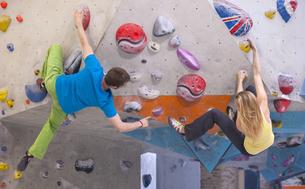 Germany, Bavaria, Munich, Young man helping woman to climbの写真素材 [FYI04341266]