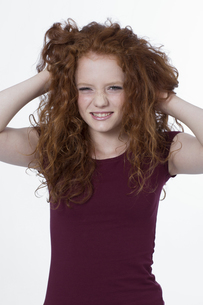 Portrait of girl pulling hair, smilingの写真素材 [FYI04341290]