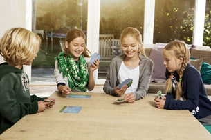 Four children playing card game in living roomの写真素材 [FYI04341309]